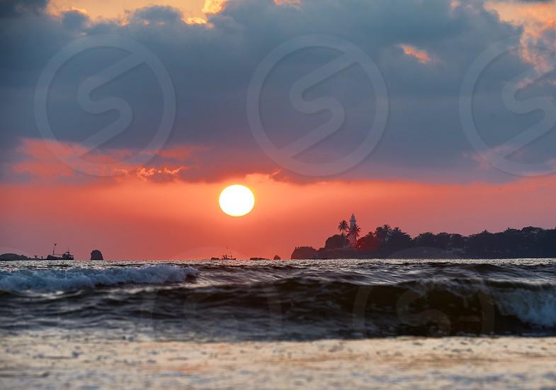 Sea sunset sun wave silhouette clouds photo