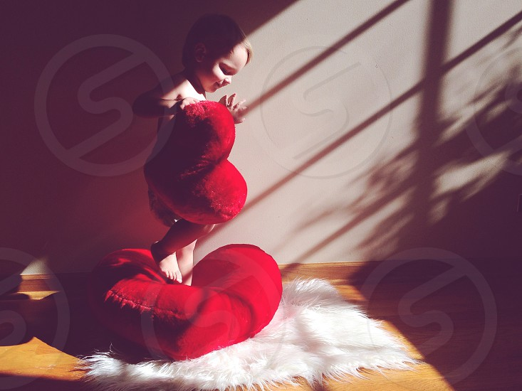 toddler standing on red heart pillow holding smaller red heart pillow photo