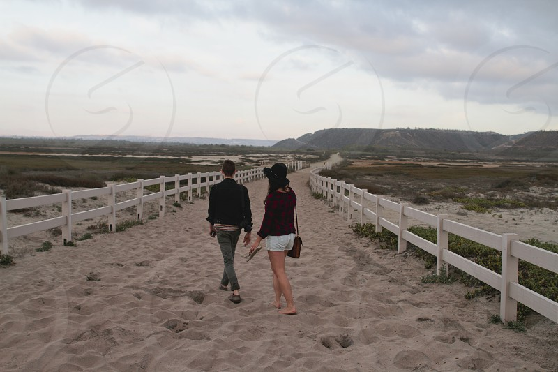 man and woman walking on gray sand photography photo