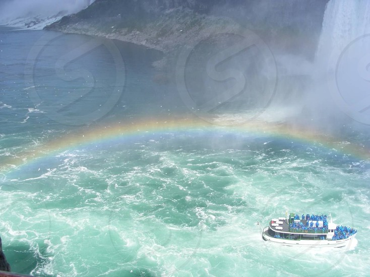 white ship sailing on sea with rainbow photo