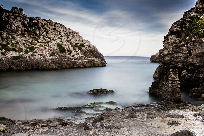 The calm sea between the rocks. The sea of Salento Italy in a spring sunset. Shot made with the technique of long exposure. photo
