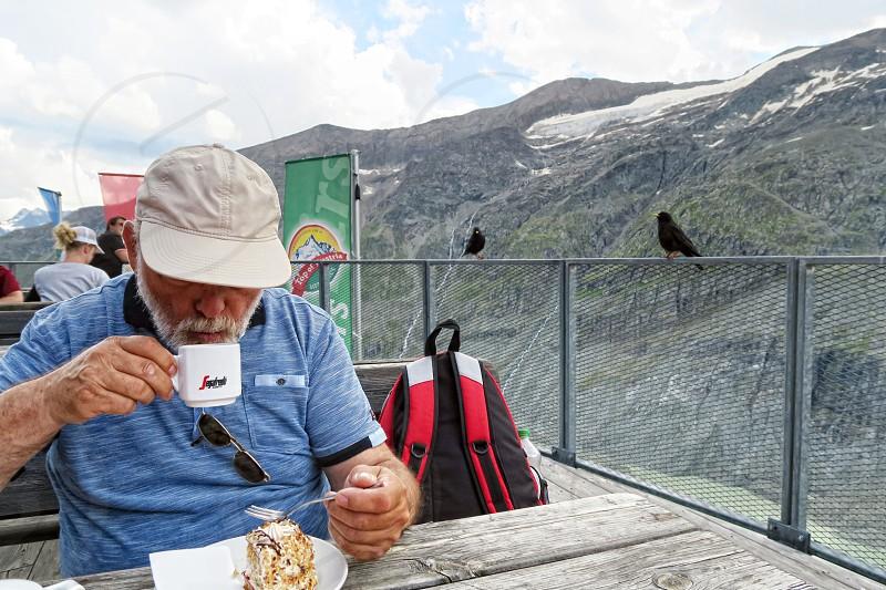 Grossglockner SALZBURGER LAND/ AUSTRIA July 30 2016: hiker resting in a restaurant at path of Grossglockner Mountain and Pasterze in Austria.  photo