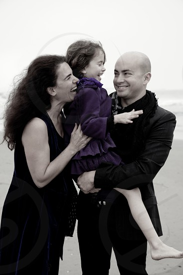 low saturated photo of woman in black tank dress beside man in black scarf and black formal suit and black pants holding girl in purple dress photo