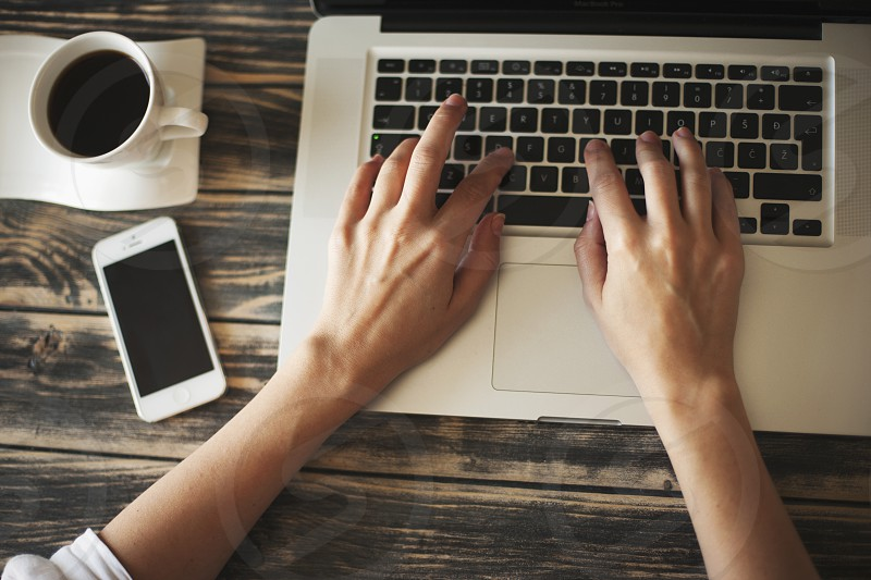 Young woman typing on laptop with coffee and mobile phone beside on a wooden table photo