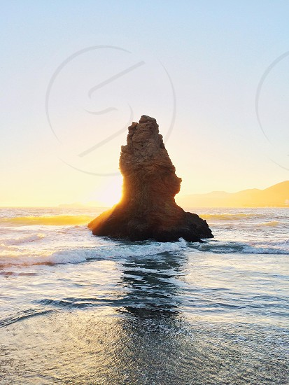 brown and black rock in sea shore with sunrise view photo