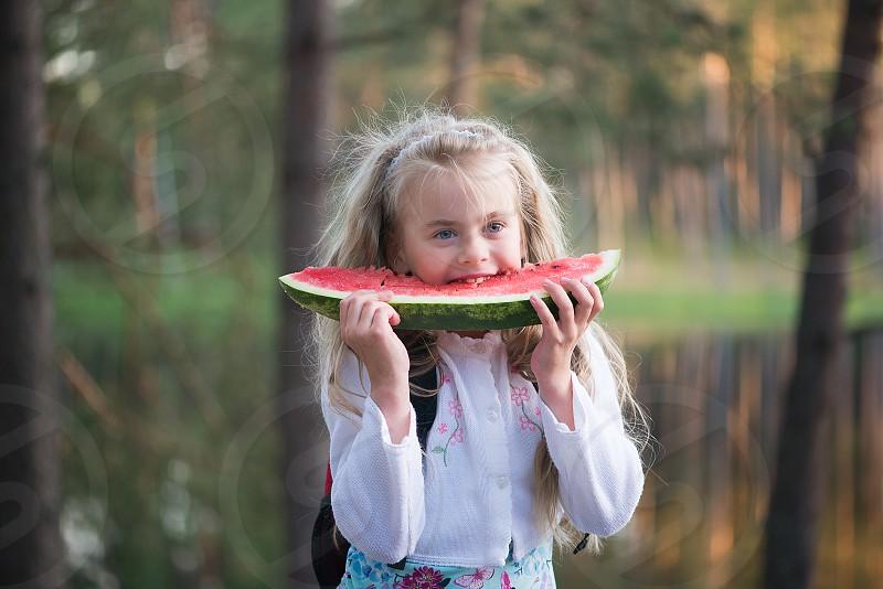 Little beautiful girl eating watermelon photo
