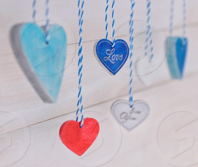 Colored hearts on white wooden background photo