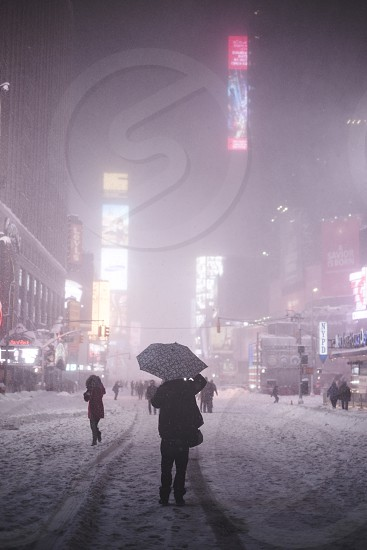people in snowy time square photo