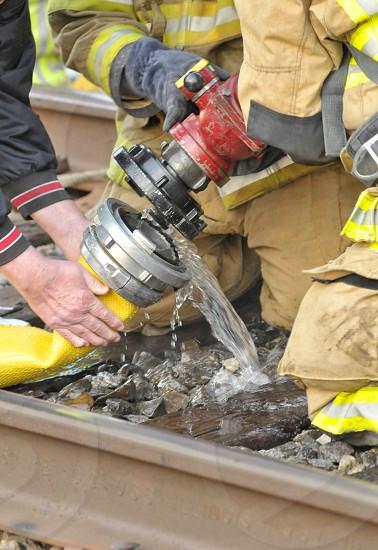 Fire fireman firemen smoke water train emergency 911 firefighter hose connected tracks  photo