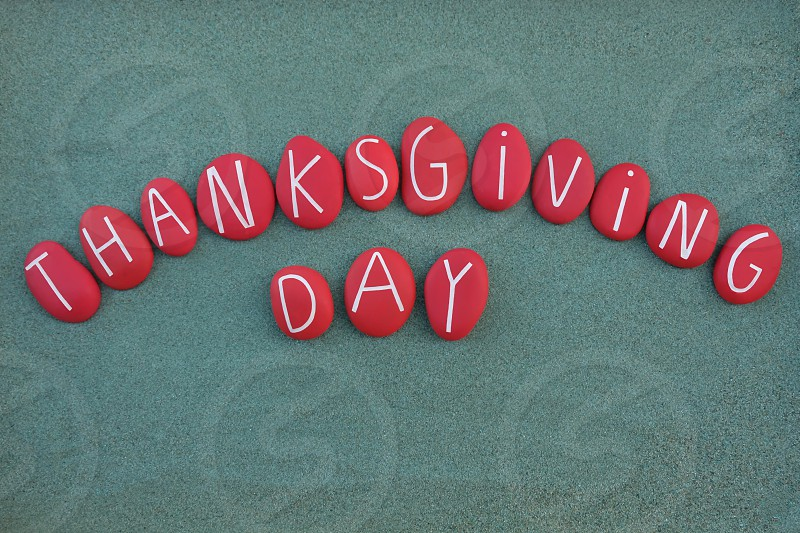 Thanksgiving Day celebrated with a creative composition of red colored stone letters over green sand photo