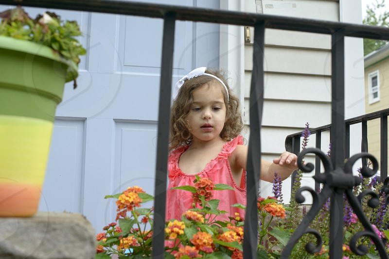 girl in pink tank top standing in porch with blooming flowers photo