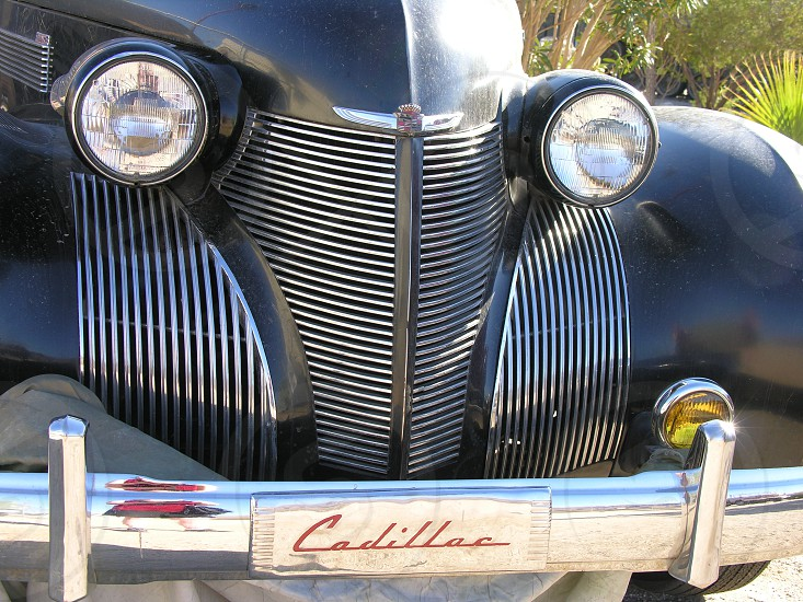 Closeup of grill and front of old black stylish classic car; Large headlights chrome bumper perpendicular grill pieces photo
