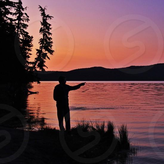 man standing near lake photo