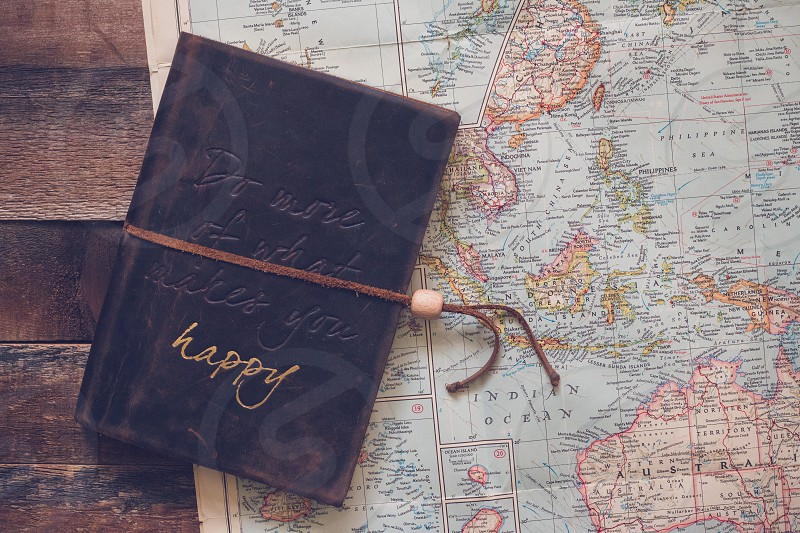 Vintage map showing the Pacific ocean islands and Australia with a leather-bound journal that says 'Do more of what makes you happy' photo