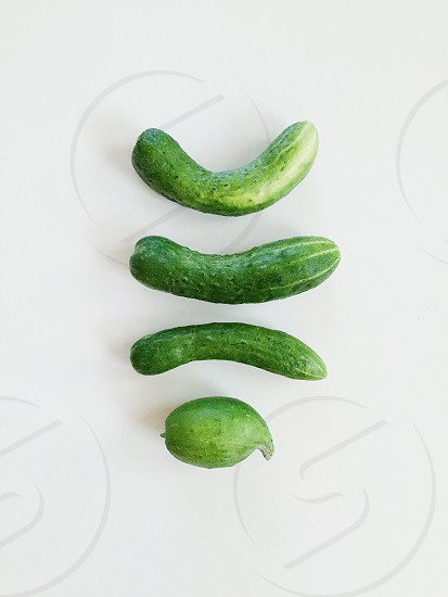 4 green cucumber on white table photo