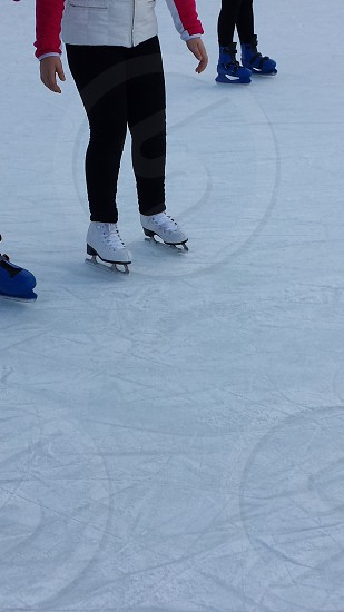 person in white ice skates shoes ice skating rink photo