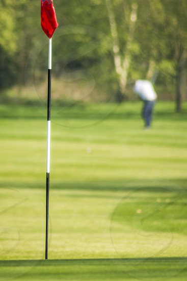 A golfer out of focus in the background plays his shot towards the flag in focus in the forground. Portrait orientation  photo