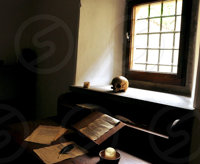 Medieval monastery cell with wooden writing desk manuscripts candles quill pen and a skull on sunlighted windowsill photo