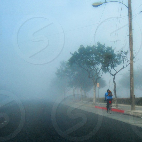 Bike riding in the fog on an urban street photo