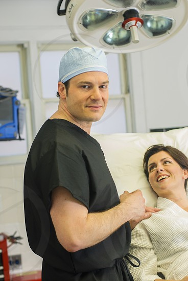 smiling man in black scrub suit touching right shoulder of smiling woman lying on white bed photo