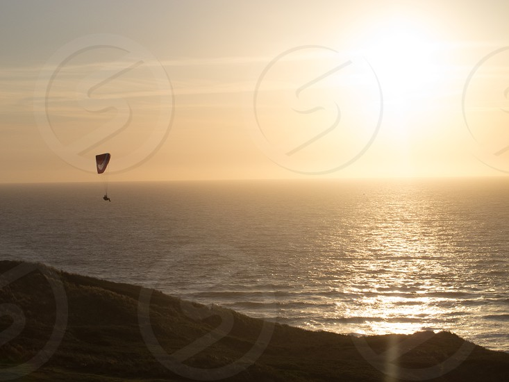 person with parachute on water during sunset photo