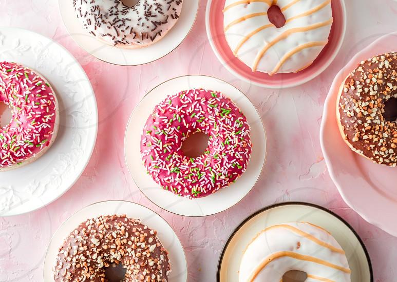 Glazed donuts on a pink background photo