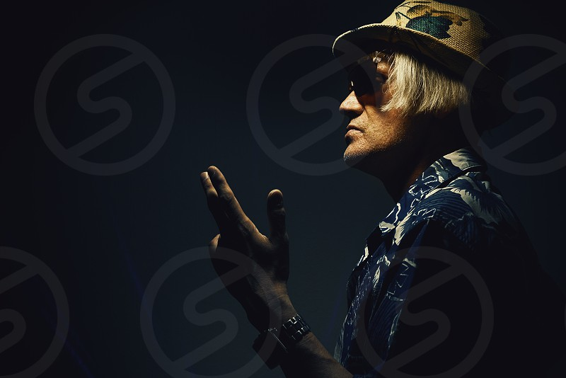Middle aged man in colorful clothes and sunglasses with modern haircut. photo