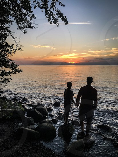Silhouette of father and daughter watching sunset over the lake photo