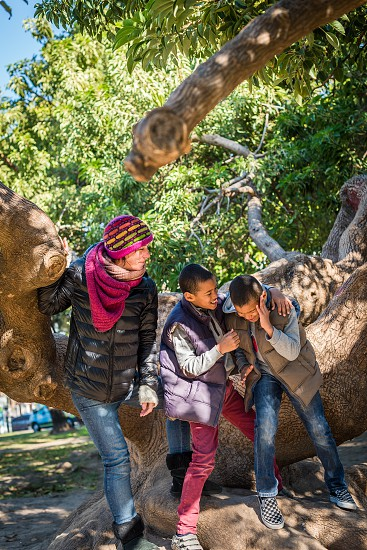 family of mother and twin kids with light dark skin color having fun and fooling around outside at the park at autumn time  photo