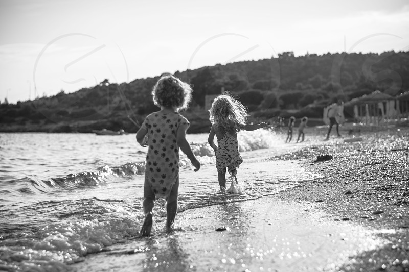 Pure happiness. Little boy and girl running across the water on beach. Childhood memories. photo