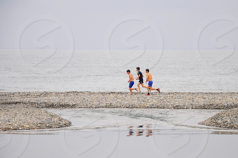3 men running through sand beside body of water photo