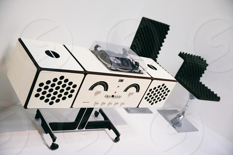 white wooden desk with vinyl disc player beside black bar stool photo