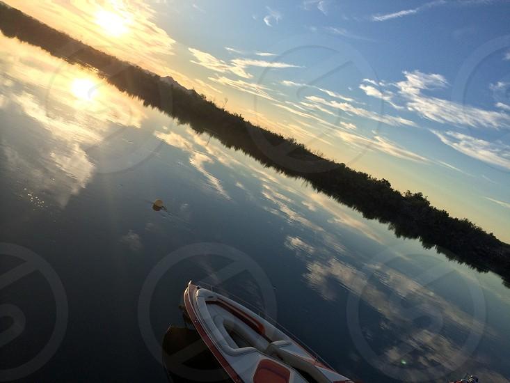 River. Boat. Reflection. Sunrise. Blue. Skies. Clean. Slick. Diagonal. Lifted. Still. photo