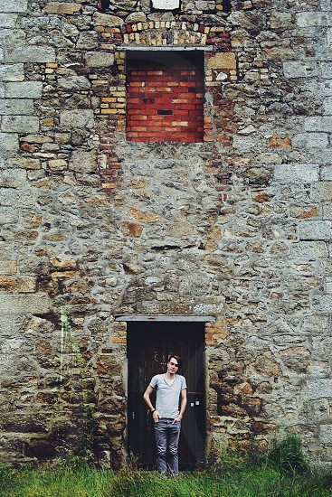 man in v neck grey shirt standing in front of white stone wall photo