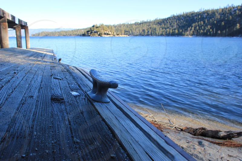wooden dock with mooring bollard and a view of forest photo