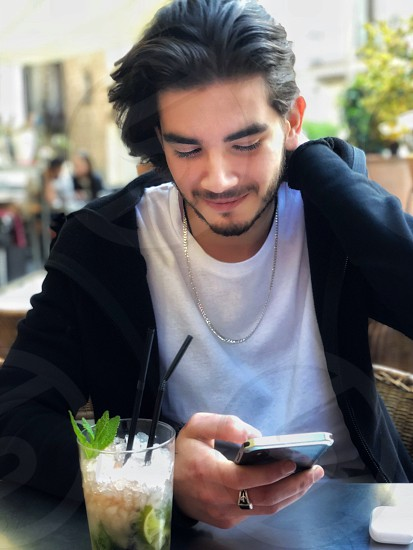 A young man sits at a table in a street cafe and smiles communicating on the phone. Before him is a glass of mojito. photo