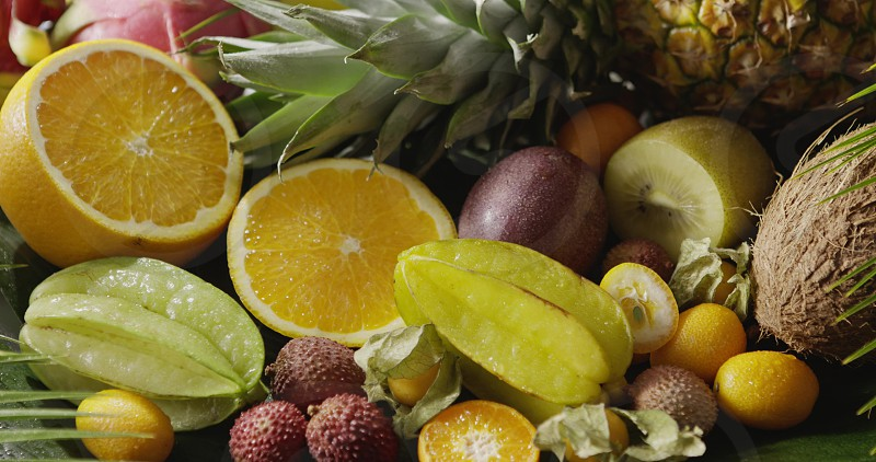 Pouring water on a fresh organic natural exotic fruits. Close-up video. Panoramic motion 4K UHD video 3840 2160p. Concept of vegetarian diet eating. photo