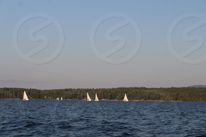 4 white sailboats across body of water under dark clouds photo