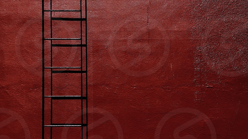 black metal ladder and red concrete wall photo