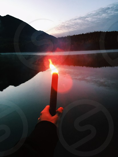 person holding torch in front of body of water during daytime photo