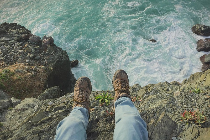 person in blue pants sitting on cliff by the sea photo