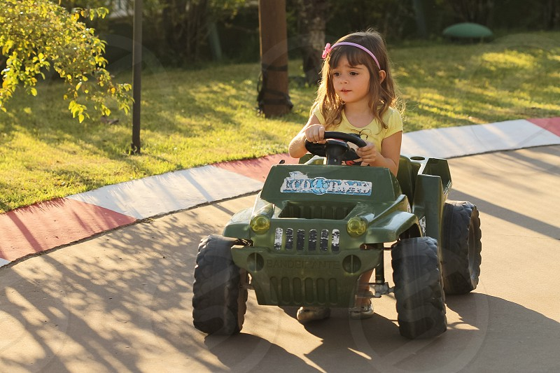 girl in yellow short sleeved shirt riding a green toy vehicle photo