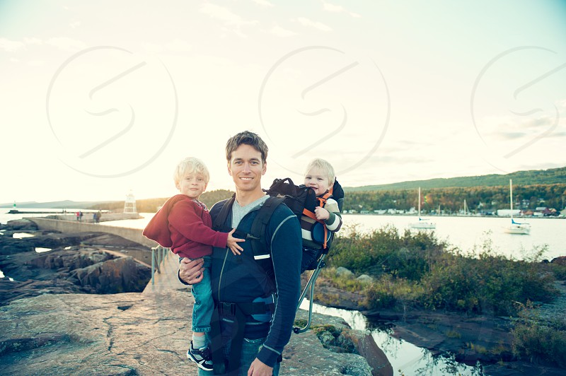 active family hiking walking adventure outdoors lake ocean sailboats pier rock backpack boys children exercise smile children dad male photo