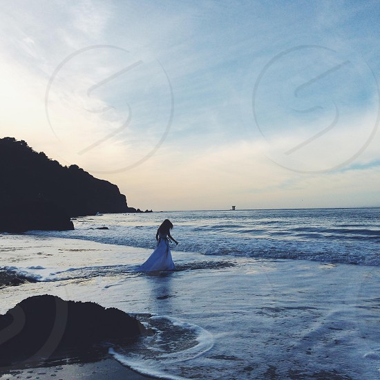 Woman wearing a white gown walking into the sea photo