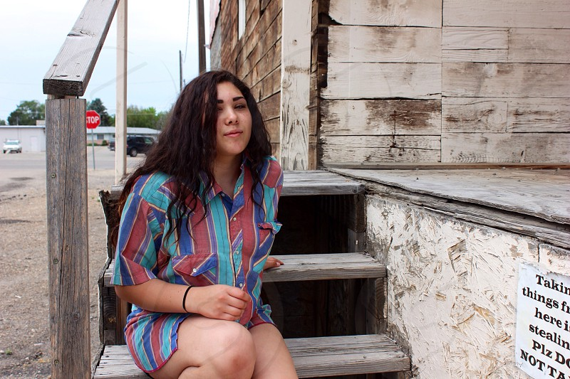 woman sitting on gray wooden stairway wearing blue teal and red striped elbow sleeve shirt during daytime photo