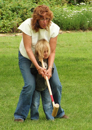 woman helping a child to bat photo