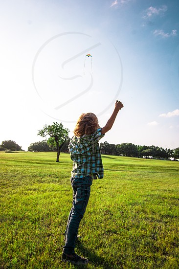 Boy youth young flying kite sunset park walking grass photo