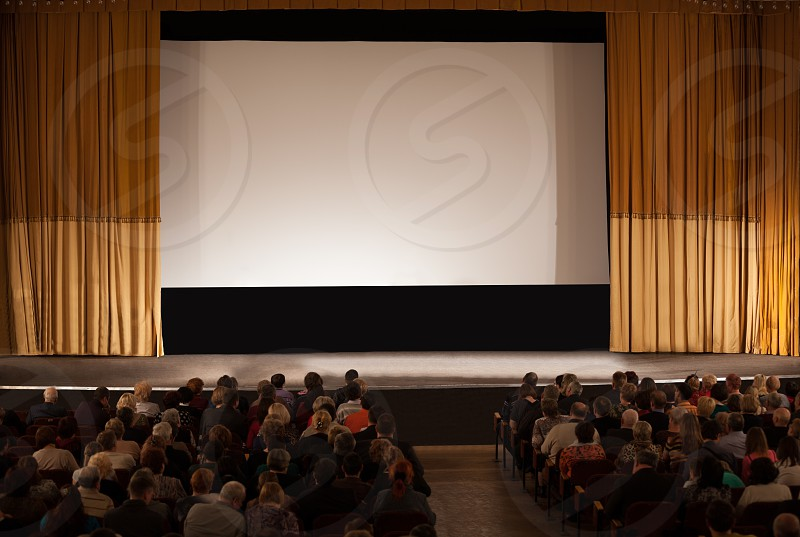 Audience seated in an auditorium in front of a stage with a screen and open curtains waiting for the start of a film or live performance photo