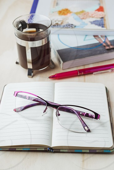 Woman glasses with notebook coffee pencil and book photo