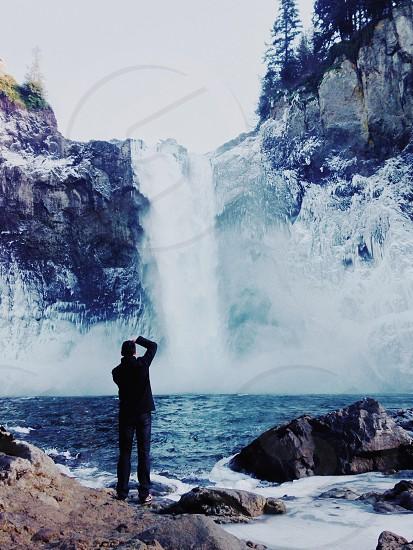 man taking picture of waterfalls photo